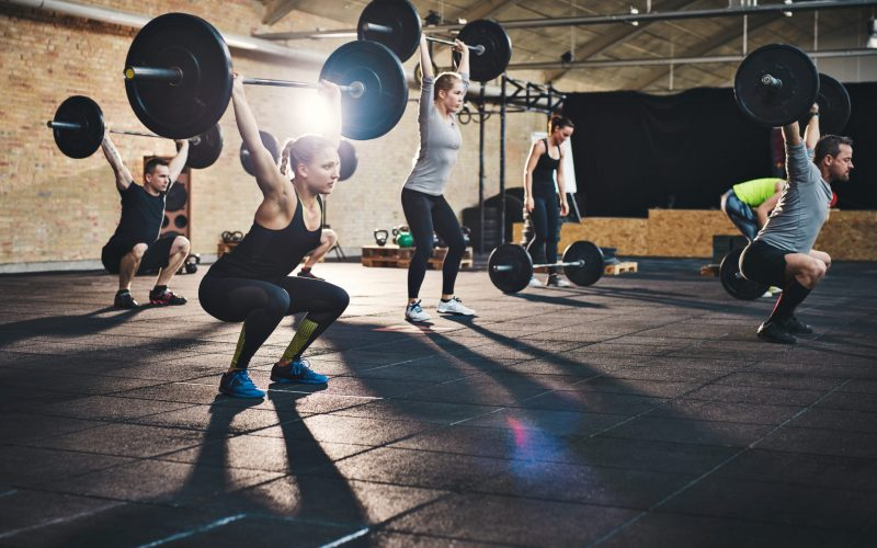 Group of young muscular adult male and females lifting large barbells in gym class with thick mats and brick walls