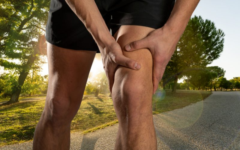 Young fit man holding knee with hands in pain after suffering muscle injury broken knee pain sprain or cramp during outdoors running. In Body pain and sport training injury and body health care.